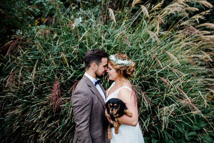 Bride and groom and puppy dog outdoors
