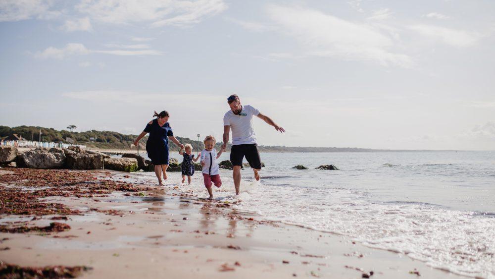 Family at Avon Beach Dorset running on the shore