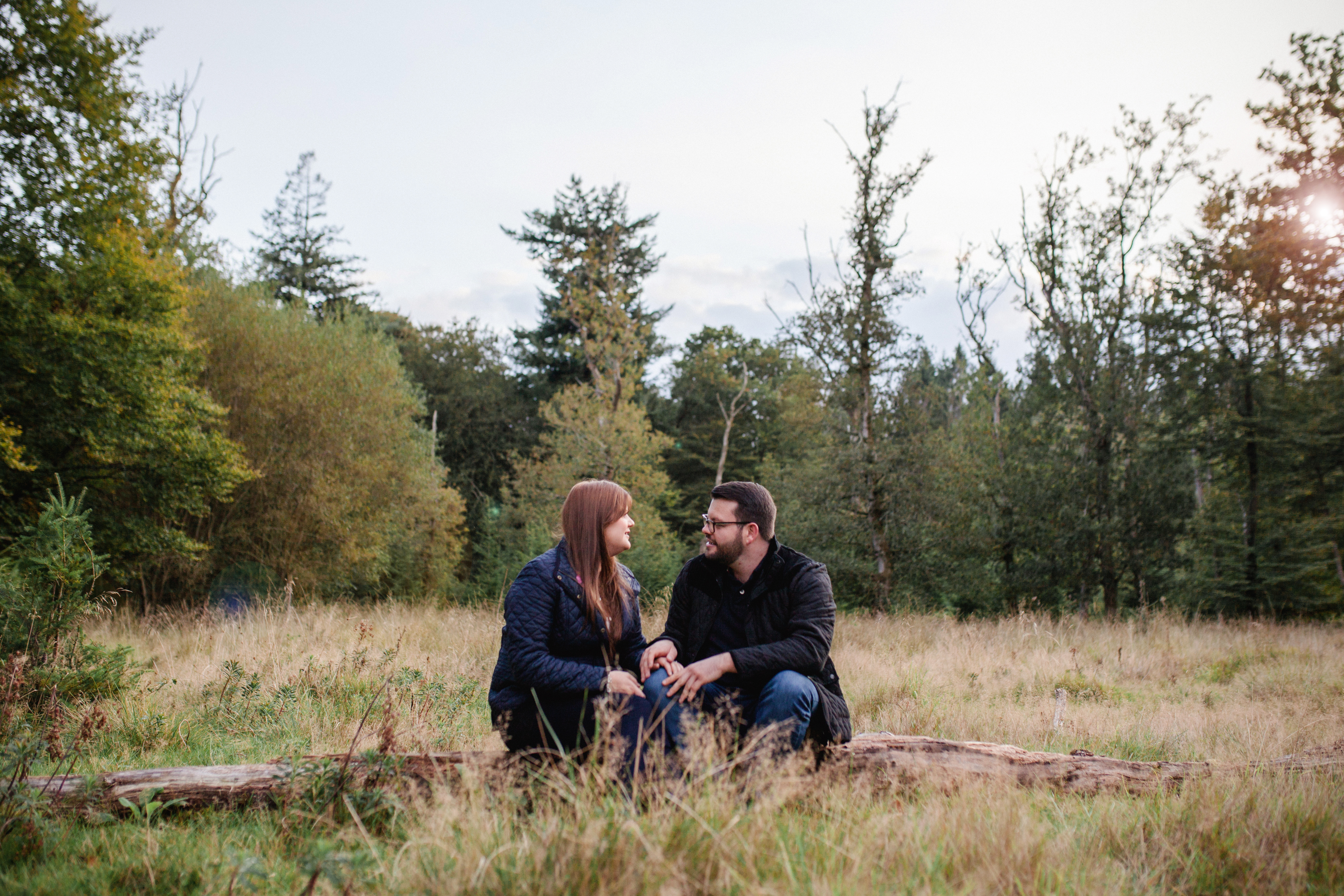 Engaged couple in the New Forest sitting together